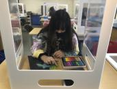 A student works on an art project while surrounded by plexiglass during class at the Sinaloa Middle School in Novato, Calif. on Tuesday, March 2, 2021. The school just reopened Monday, Feb. 22, 2021 for in-person learning. (AP Photo/Haven Daily)