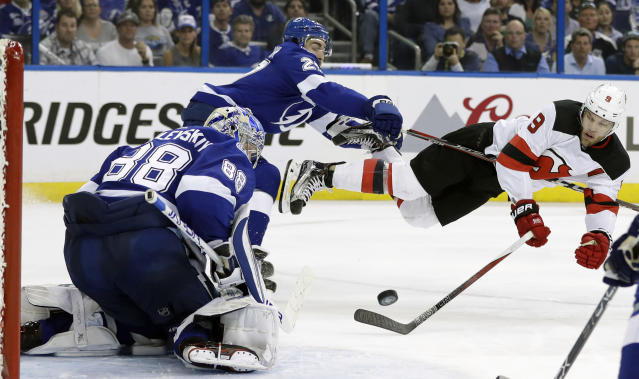 Tampa Bay Lightning defenseman Ryan McDonagh (27) sends New Jersey Devils left wing Taylor Hall (9) flying after Hall shot against goaltender Andrei Vasilevskiy (88) during the third period of Game 5 of an NHL first-round hockey playoff series Saturday, April 21, 2018, in Tampa, Fla. (AP Photo/Chris O'Meara)