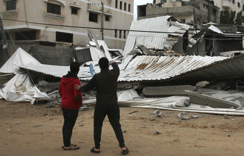 Palestinians inspect the damage of destroyed building belongs to Hamas ministry of prisoners hit by Israeli airstrikes in Gaza City early Friday Friday