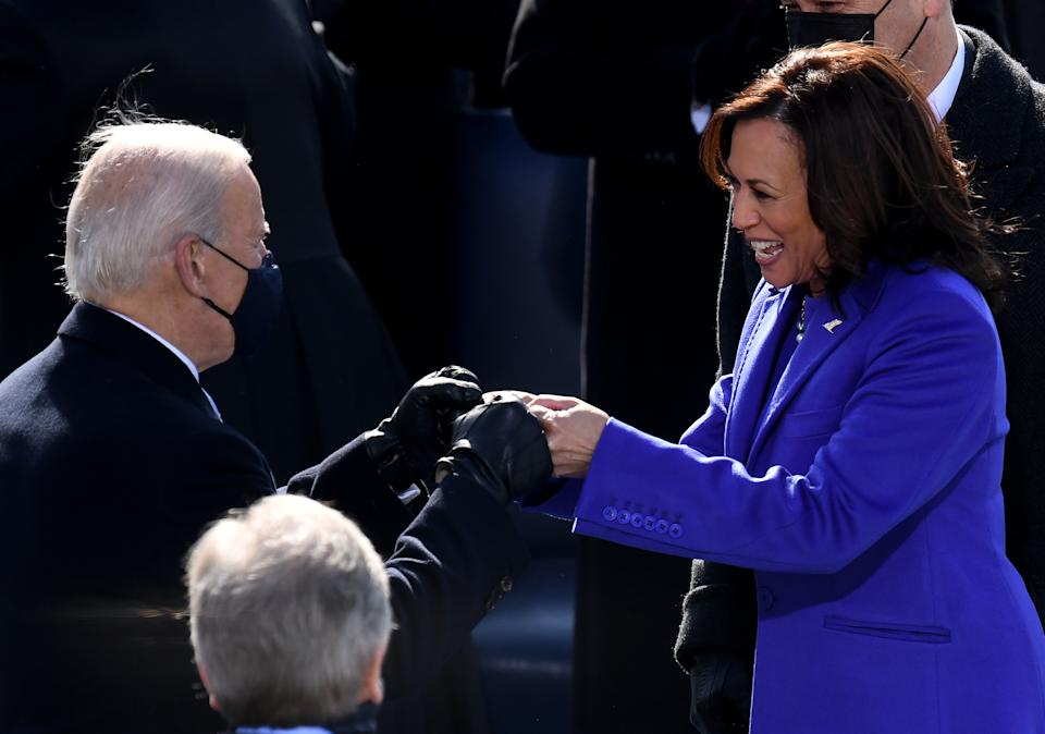 TOPSHOT - US Vice President Kamala Harris bumps fists ahead of the inauguration of Joe Biden as the 46th US President on January 20, 2021, at the US Capitol in Washington, DC. (Photo by OLIVIER DOULIERY / AFP) (Photo by OLIVIER DOULIERY/AFP via Getty Images)