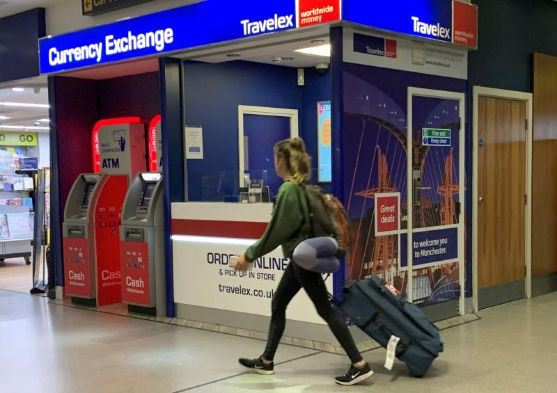 FILE PHOTO: A passenger walks past a Travelex currency exchange at Manchester Airport in Manchester, Britain