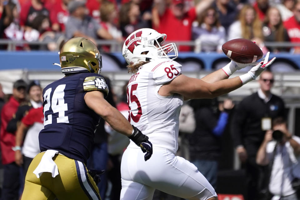 Wisconsin tight end Clay Cundiff (85) catches a pass as Notre Dame linebacker Jack Kiser defends during the first half of an NCAA college football game Saturday, Sept. 25, 2021, in Chicago. (AP Photo/Charles Rex Arbogast)