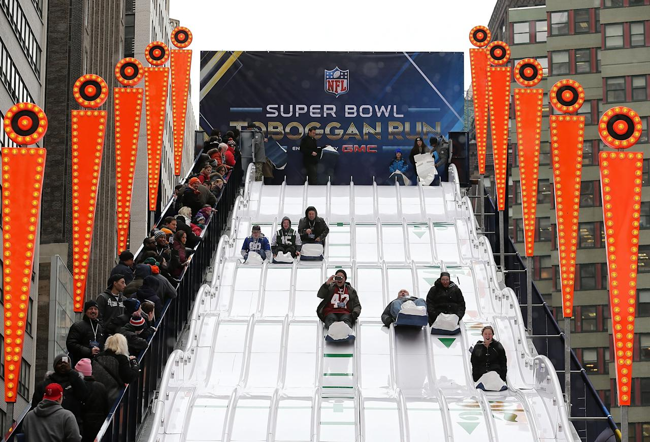 NEW YORK CITY, NY - JANUARY 31: People slide down the NFL toboggan run in Times Square on January 31, 2014 in New York City. Broadway has temporarily been re-named Super Bowl Boulevard as the city prepares for Sunday's game between the Denver Broncos and Seattle Seahawks. (Photo by Christian Petersen/Getty Images)