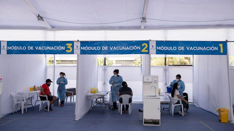 Health workers give the Chinese CoronaVac vaccine against COVID-19 at a vaccination centre in Santiago, on March 24, 2021. - Chilean authorities have been implementing, among other measures, a selective quarantine in areas with a high incidence of infection and have placed an emphasis on controlling the pandemic by mass screening. (Photo by Martin BERNETTI / AFP) (Photo by MARTIN BERNETTI/AFP via Getty Images)