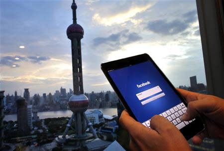 Photo illustration of man holding iPad with a Facebook application in an office building at the Pudong financial district in Shanghai