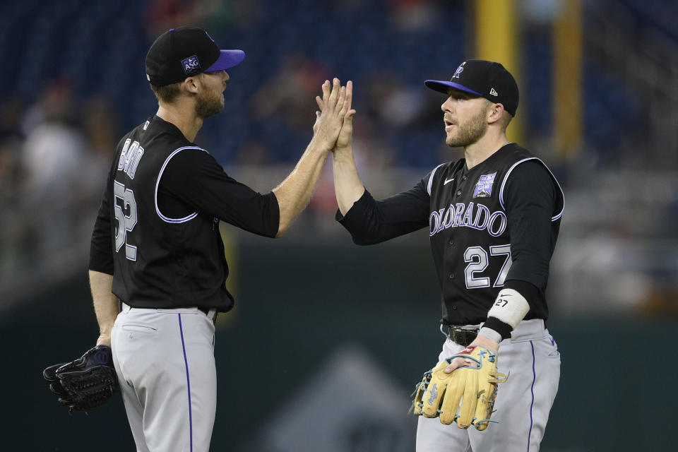 Colorado Rockies' Trevor Story (27) celebrates with Daniel Bard (52) after a baseball game against the Washington Nationals, Saturday, Sept. 18, 2021, in Washington. (AP Photo/Nick Wass)