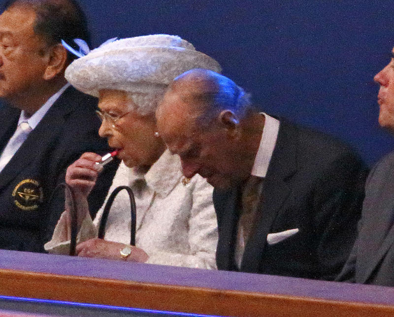 Queen Elizabeth II puts on her lip stick as she and Prince Philip, Duke of Edinburgh attend the Opening Ceremony for the Glasgow 2014 Commonwealth Games. [Photo: Getty]