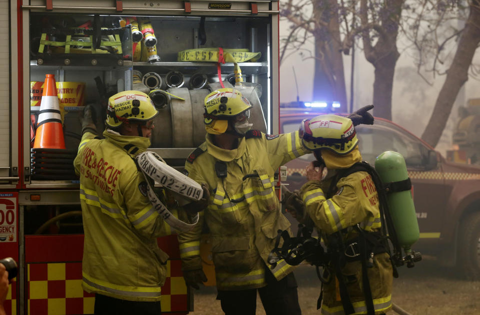 Firefighters work to save a house on Bullocky Way, Possum Brush, south of Taree in the Mid North Coast region of NSW.