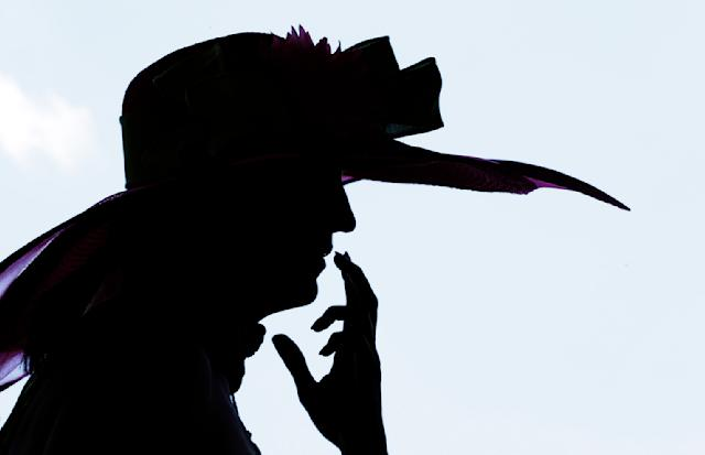 A woman watches a race before the 140th running of the Kentucky Derby horse race at Churchill Downs Saturday, May 3, 2014, in Louisville, Ky. (AP Photo/Charlie Riedel)