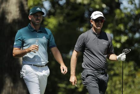 Sergio Garcia of Spain (L) and Justin Rose of England walk up the second fairway in final round play during the 2017 Masters golf tournament at Augusta National Golf Club in Augusta, Georgia, U.S., April 9, 2017. REUTERS/Jonathan Ernst