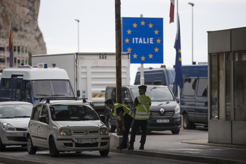 FILE - In this Monday, June 15, 2020 file photo, French gendarmes approach a car at the Saint-Ludovic border check point on the Franco-Italian border in Menton, France. The European Union is set to make public Tuesday June 30, 2020, a list of countries whose citizens will be allowed to enter 31 European countries, but most Americans are likely to be refused entry for at least another two weeks due to soaring coronavirus infections in the U.S.  (AP Photo/Daniel Cole, File)