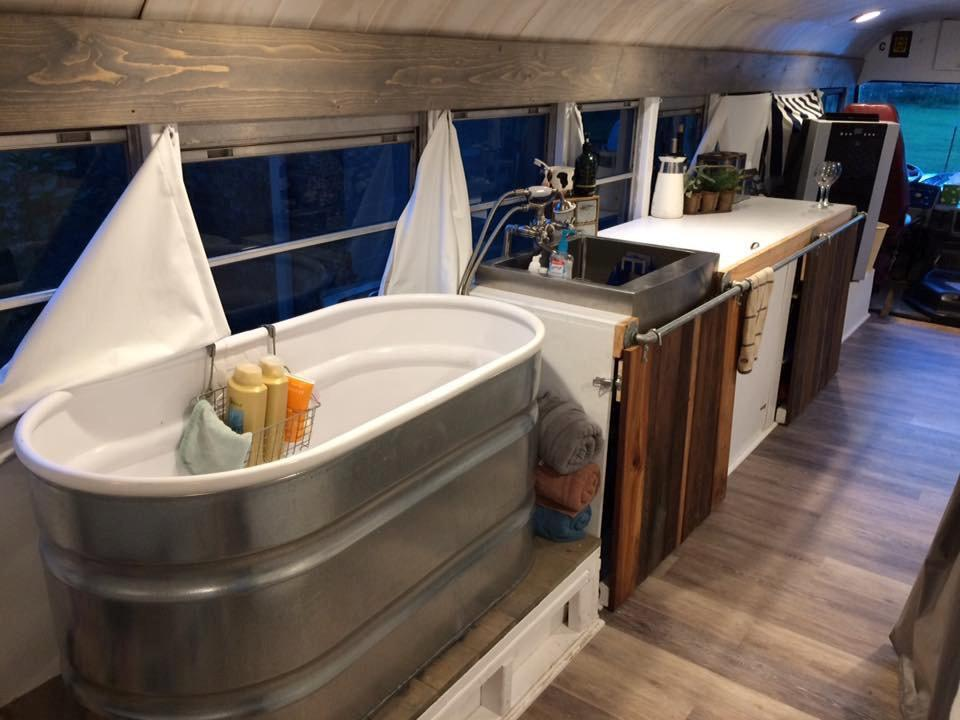 """<p>The huge bath tub is a converted livestock trough the couple bought for $80. Amy said: """"When we were renovating the bus, a bathtub was the number one priority for me. I am a bath person and I told him once I have a bathtub and a comfortable bed, I will be okay. I can live without a couch."""" [Picture: SWNS] </p>"""