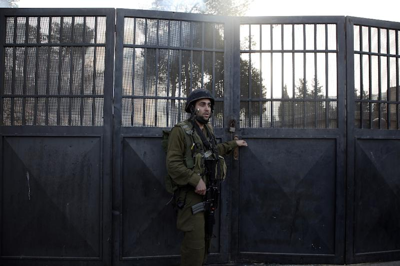 A member of the Israeli security forces stands guard at the main entrance of a Palestinian school that has been ordered by Israel to be shut down, in the town of as-Sawiyah, south of Nablus in the occupied West Bank on October 15, 2018