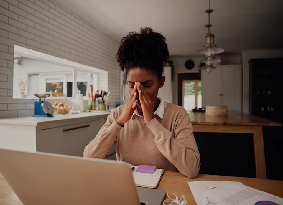 Stressed businesswoman holding head working on laptop