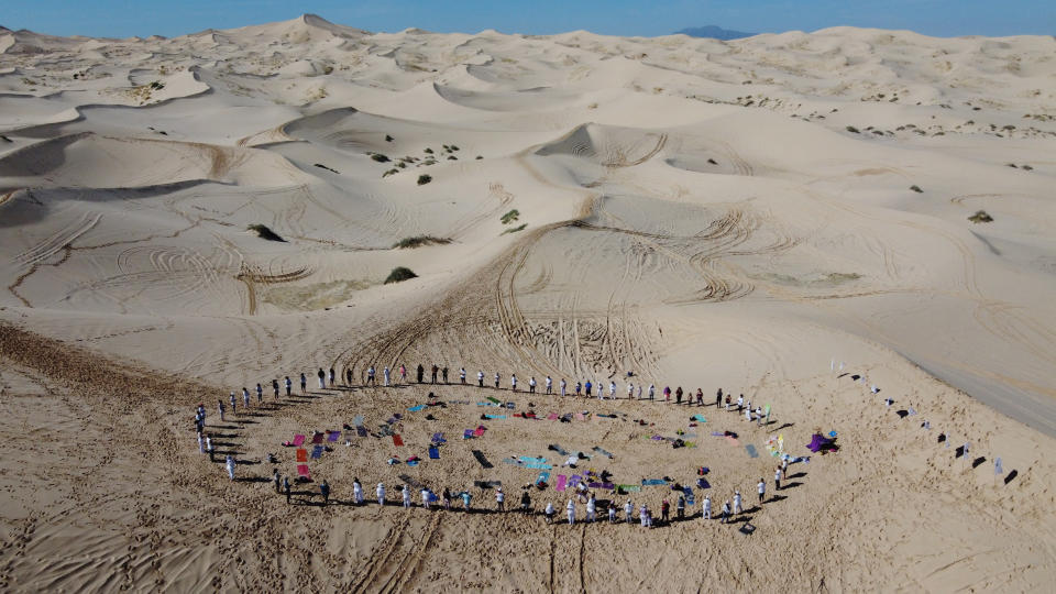 People stand in a circle as they take part in the sixth annual Yoga Meeting in the Samalayuca Dunes, on the outskirts of Ciudad Juarez, Mexico, Saturday, July 3, 2021. This year yoga enthusiasts attended the outdoor event as a symbol of hope for those who survived the coronavirus and honoring those who have died from complications related to COVID-19. (AP Photo/Christian Chavez)