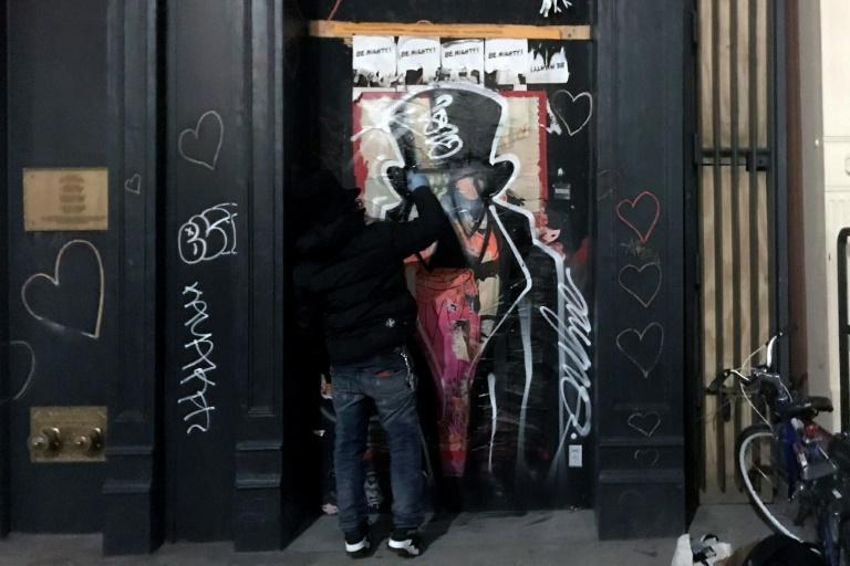 Graffiti artist Saynosleep painting on a storefront in New York in December 2020