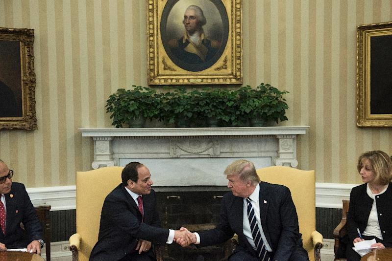 Translators watch as Egypt's President Abdel Fattah al-Sisi (L) and US President Donald Trump shake hands in the Oval Office before a meeting at the White House April 3, 2017 (AFP Photo/Brendan Smialowski)