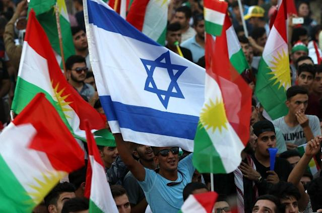 <p>An Israeli flag is waved alongside Kurdish flags during an event in Iraqi Kurdistan's capital of Arbil on Sept. 16, 2017, to urge people to vote in a Sept. 25 independence referendum. (Photo: Safin Hamed/AFP/Getty Images) </p>