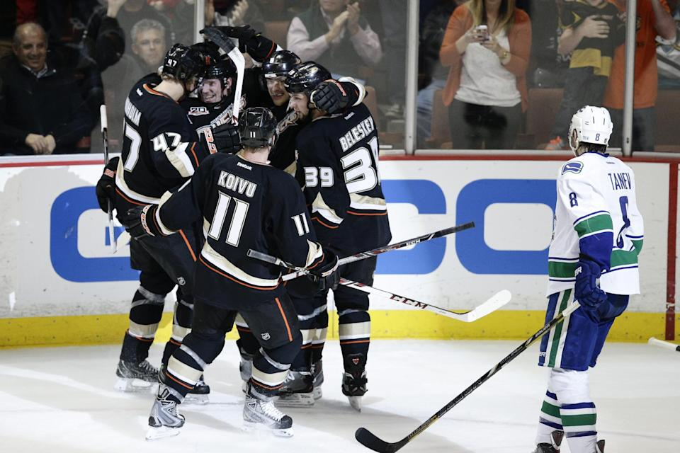 The Anaheim Ducks players celebrate a goal by Teemu Selanne (8), of Finland, next to Vancouver Canucks' Chris Tanev, right, during the first period of an NHL hockey game on Wednesday, Jan. 15, 2014, in Anaheim, Calif. (AP Photo/Jae C. Hong)