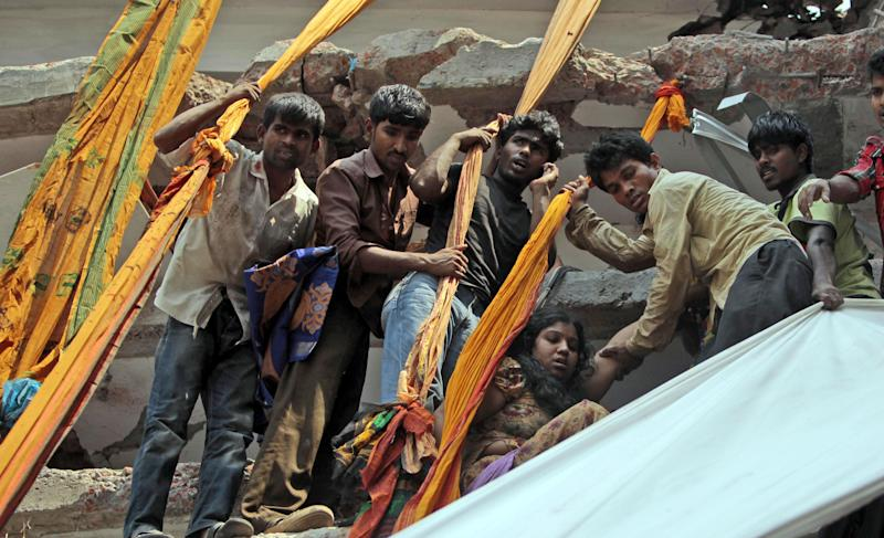 Rescue workers use clothing to lower down survivors from the site of a building that collapsed in Savar, near Dhaka, Bangladesh, Wednesday, April 24, 2013. An eight-story building housing several garment factories collapsed near Bangladesh's capital on Wednesday, killing dozens of people and trapping many more under a jumbled mess of concrete. Rescuers tried to cut through the debris with earthmovers, drilling machines and their bare hands. (AP Photo/A.M.Ahad)