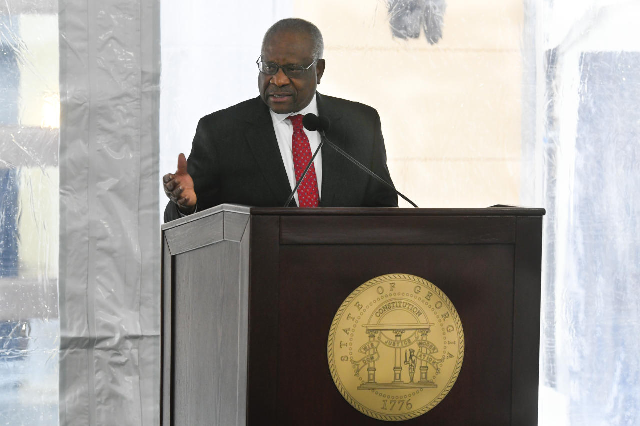 Supreme Court Associate Justice Clarence Thomas motions to former Georgia Governor Nathan Deal while delivering a keynote address during a dedication of the state's new Nathan Deal Judicial Center, Tuesday, Feb. 11, 2020, in Atlanta. The ceremony, due to rain, was held in a tent outside the new center which is being named for the former governor and is the first state building in the history of Georgia that is devoted entirely to the judiciary. (AP Photo/John Amis)