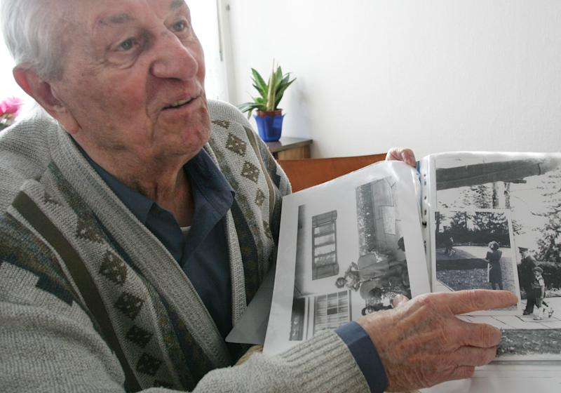 FILE - In this March 10, 2005 file photo Hitler's bodyguard Rochus Misch points on a picture of Adolf Hitler he had taken in Berchtesgarden, southern Germany, in the early 1940th in his house in Berlin. Misch, who was the last remaining witness to the Nazi leader's final hours in his Berlin bunker, has died Thursday, Sept. 5, 2013. He was 96. (AP Photo/Herbert Knosowski, File)