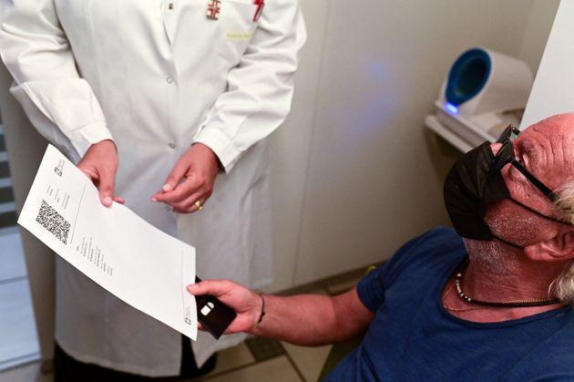 Zacco Cataldo, 70 years old receives a document proving his vaccination against the Covid-19, on August 5, 2021 at the Ambreck pharmacy, in Milan. - The Green Pass enters into force in Italy on August 6, 2021. (Photo by MIGUEL MEDINA / AFP) (Photo by MIGUEL MEDINA/AFP via Getty Images) (Photo: MIGUEL MEDINA via Getty Images)