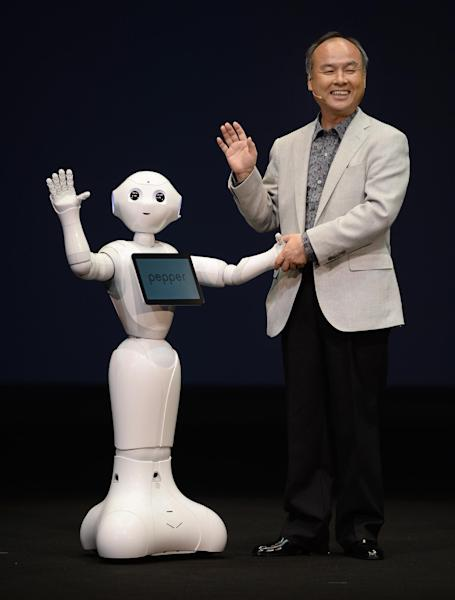 Masayoshi Son, president of Japan's mobile carrier SoftBank, introduces the humanoid robot 'Pepper', equipped with an emotion engine, during a press conference in Urayasu, suburban Tokyo, on June 5, 2014 (AFP Photo/Toru Yamanaka)