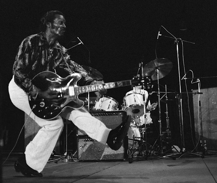 "Chuck Berry produces his famous ""duck walk"" in front of thousands gathered to see him perform on July 10, 1981, at the old theatre in Vienne, France (AFP Photo/NOVOVITCH)"