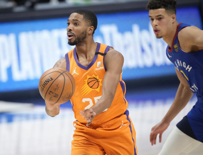 Phoenix Suns forward Mikal Bridges, left, drives past Denver Nuggets forward Michael Porter Jr. in the first half of Game 3 of an NBA second-round playoff series Friday, June 11, 2021, in Denver. (AP Photo/David Zalubowski)