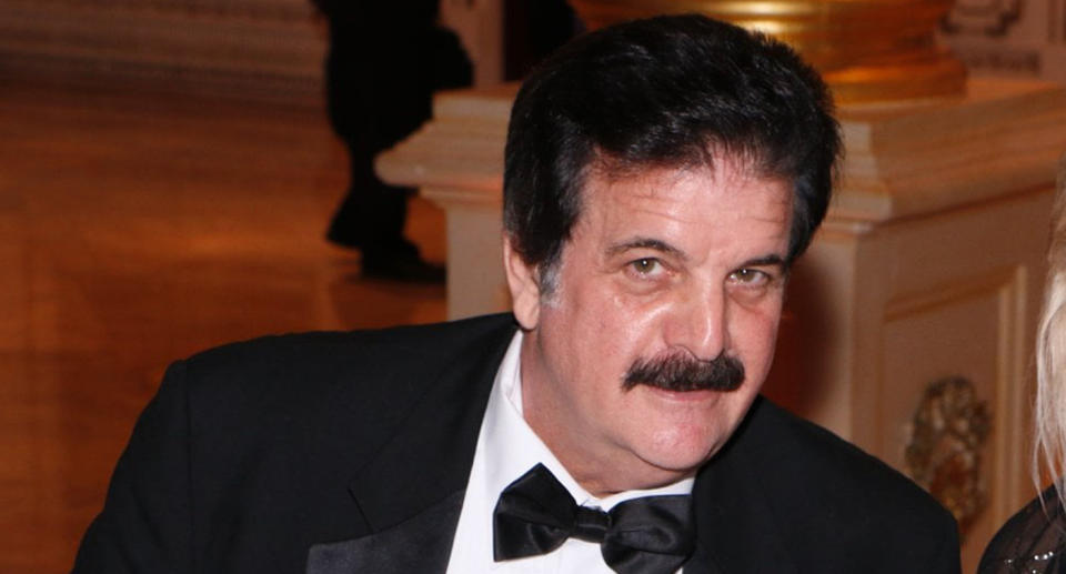 Photo of Dick Farrel, with dark hair and a moustache, wearing a suit and looking at the camera.