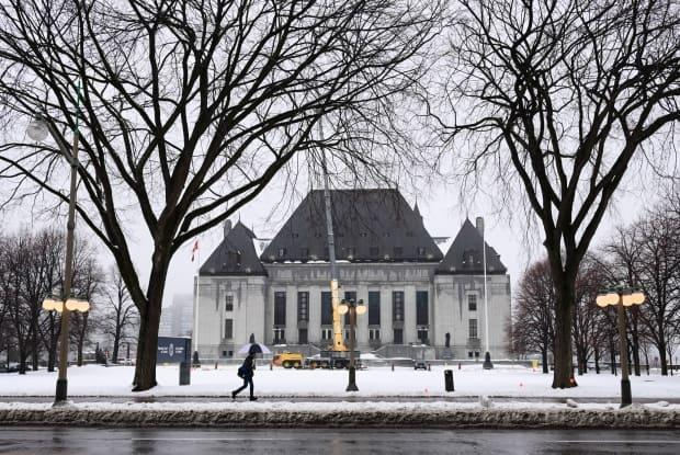 A pedestrian walks past the Supreme Court of Canada in Ottawa Nov. 26, 2020. The court will deliver its decision on a legal challenge against the federal government's carbon tax on Thursday morning. (Sean Kilpatrick/Canadian Press - image credit)
