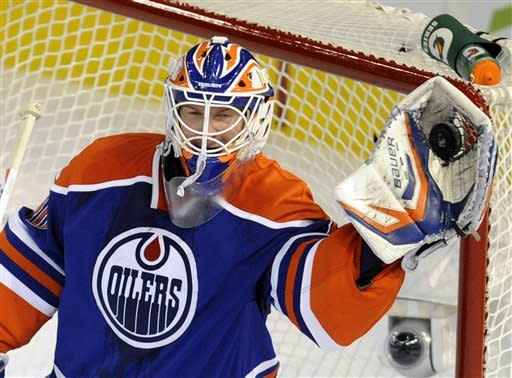 Edmonton Oilers goalie Devan Dubnyk makes a glove save against the Phoenix Coyotes during the first period of an NHL hockey game in Edmonton on Sunday, March 18, 2012. (AP Photo/The Canadian Press, John Ulan)