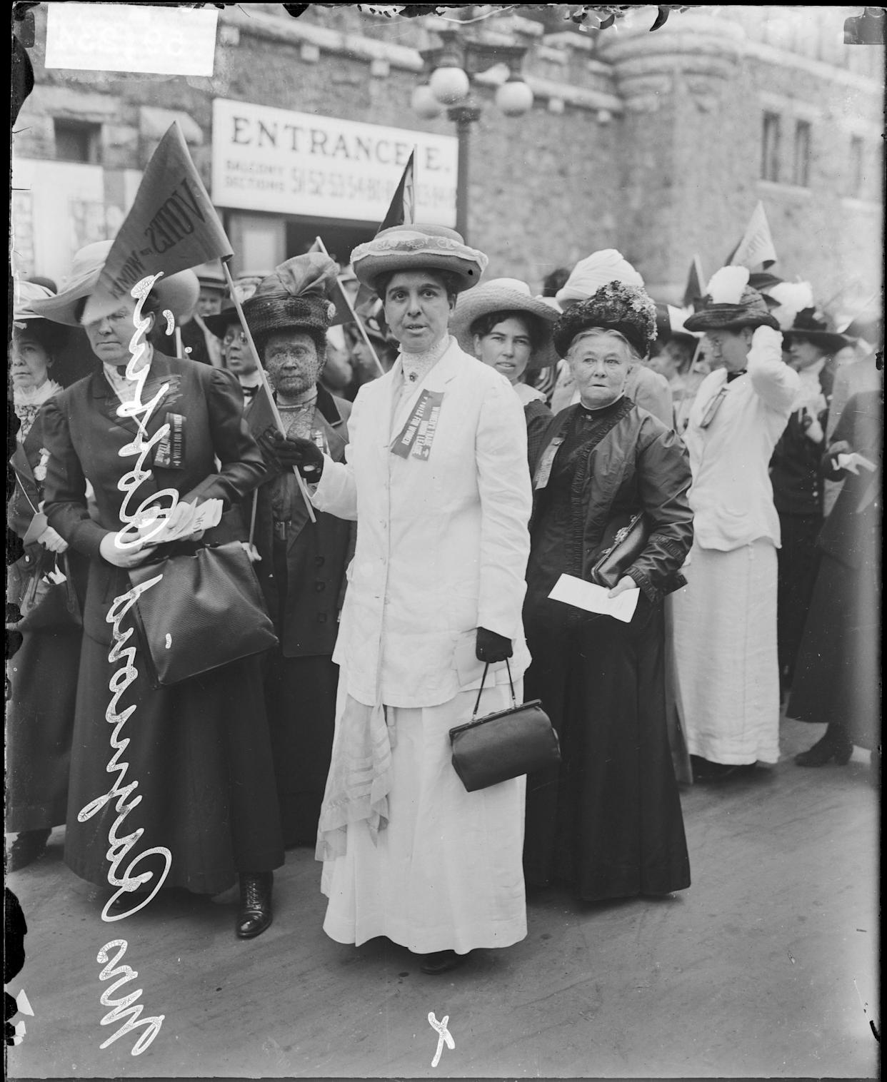 Mrs Raymond Robbins and a group of women suffragists in front of the Coliseum at the time of the Republican National Convention, Chicago, Illinois, 1912. The Coliseum was located at 1513 South Wabash Avenue. Robbins is holding a pennant that reads: 'Votes for women.' From the Chicago Daily News collection.