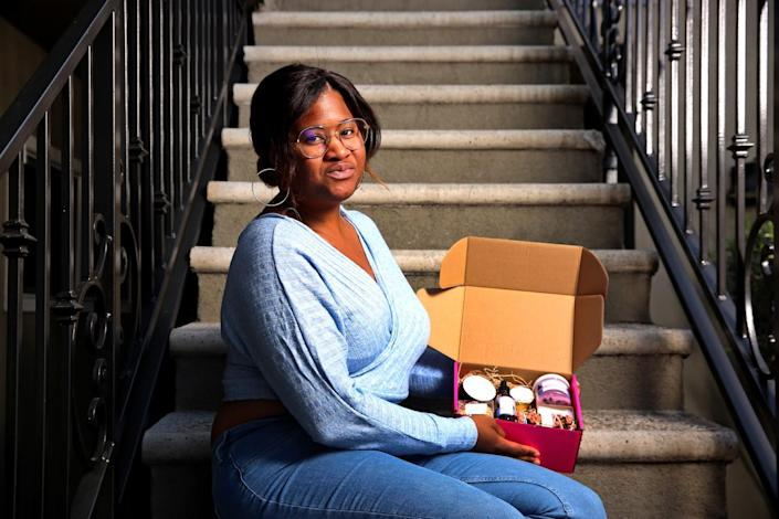 A woman seated on stairs holds a pink box of beauty products