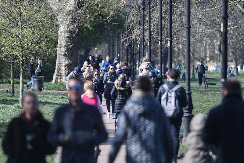 LONDON, ENGLAND - MARCH 22: People are seen walking on Clapham Common on March 22, 2020 in London, United Kingdom. British Prime Minister Boris Johnson urged that people don't visit their parents this Mothering Sunday to curb the spread of COVID-19, which has killed 233 people in the UK. (Photo by Peter Summers/Getty Images)