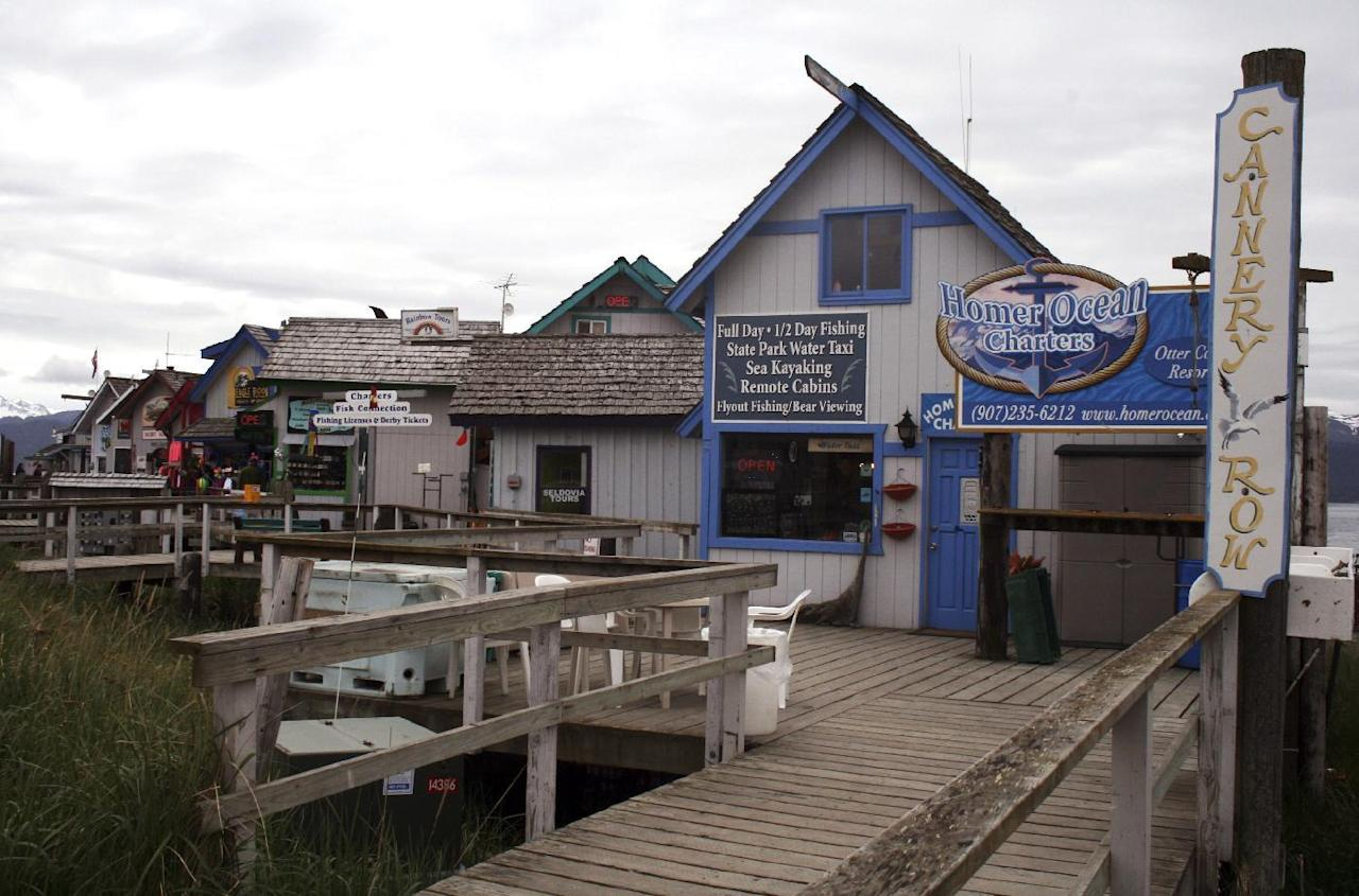 """In this May 24, 2015, photo, seasonal tourism businesses set up on the Homer Spit in Homer, Alaska. Homer is wading deeper into the national political debate, becoming the latest U.S. city to consider affirming its commitment to inclusion amid concerns about the treatment of immigrants, religious groups, the LGBTQ community and others. The City Council on Monday, Feb. 27, 2017, is expected to weigh a resolution that states Homer will resist any efforts to profile """"vulnerable populations"""" and will reject any expressions of fear and hate. (AP Photo/Mark Thiessen)"""