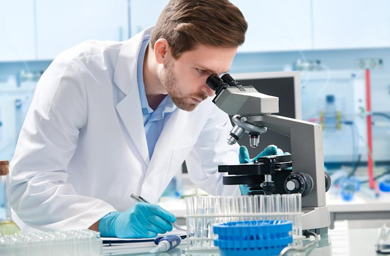 A man in lab coat and gloves looking through a microscope.