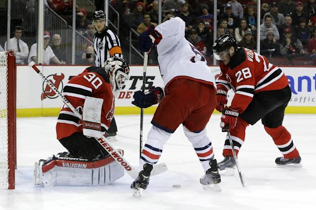 New Jersey Devils goalie Martin Brodeur, left, makes a save on a shot by Columbus Blue Jackets center Mark Letestu, center, as defenseman Anton Volchenkov (28), of Russia, defends on the play during the first period of an NHL hockey game, Friday, Dec. 27, 2013, in Newark, N.J. (AP Photo/Julio Cortez)