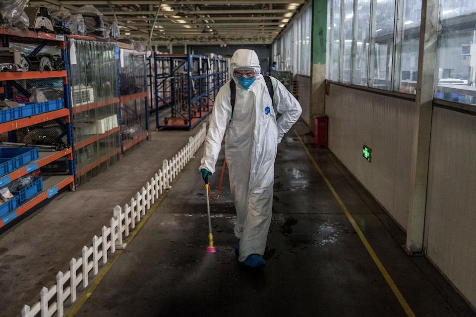 This photo taken on March 25, 2020 shows an employee spraying disinfectant at a Midea factory in Wuhan in China's central Hubei province. - China lifted tough restrictions on the province at the epicentre of the coronavirus outbreak on March 25 after a months-long lockdown as the country reported no new domestic cases. (Photo by STR / AFP) / China OUT (Photo by STR/AFP via Getty Images)