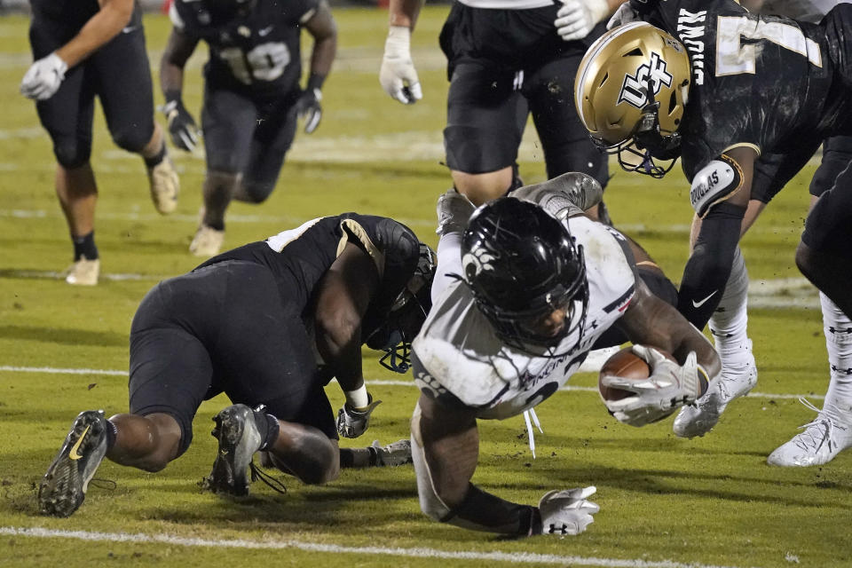 Cincinnati running back Gerrid Doaks, center, is stopped just short of the goal line by Central Florida defensive backs Derek Gainous, left, and Davonte Brown (7) during the second half of an NCAA college football game, Saturday, Nov. 21, 2020, in Orlando, Fla. (AP Photo/John Raoux)