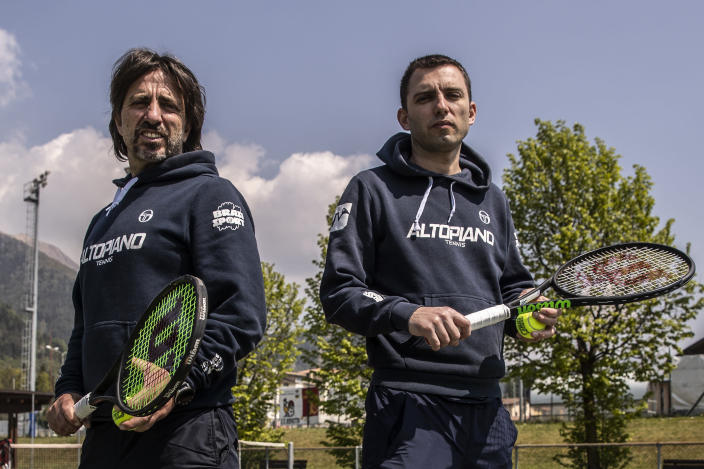 In this image take on Friday, April 24, 2020 Italian Tennis Federation coaches Daniele Brasi, 41, right, is flanked by his brother Luca Brasi, 55, as they pose for a portrait on their tennis court in Rovetta, near Bergamo, northern Italy. The brothers, who lost an uncle to COVID-19, run one of the biggest Italian Tennis Federation centers in the valley. They rely on tourism for about 50% of their yearly income, the rest comes from roughly 900 school students who follow courses throughout the winter, including some 20 under-18 professionals. (AP Photo/Luca Bruno)
