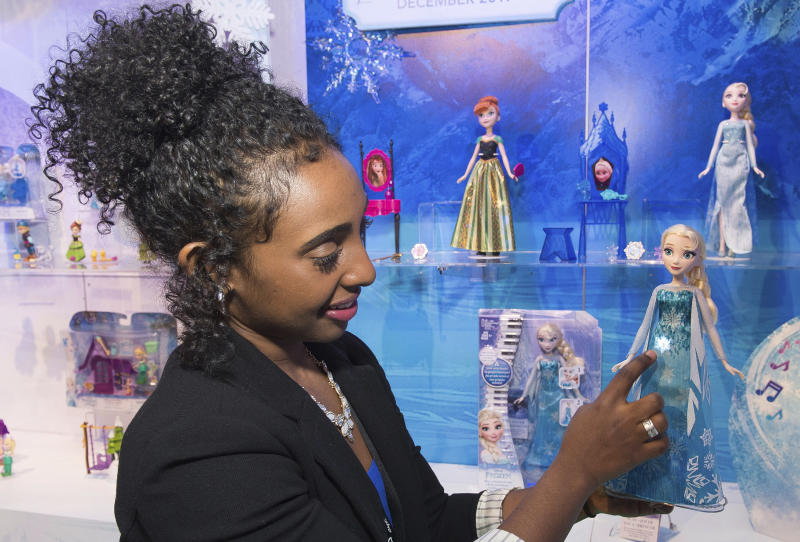 "IMAGE DISTRIBUTED FOR HASBRO on 2/19 - A demonstrator in the Hasbro, Inc. showroom during the American International Toy Fair showcases the DISNEY FROZEN PLAY-A-MELODY ELSA doll which enables kids to play the hit song ""Let It Go"" as well as songs of their own creation in New York. The musical gown on the DISNEY FROZEN PLAY-A-MELODY ELSA doll doubles as a keyboard with light up snowflake keys and provides kids with three different ways to play music. (Photo by Charles Sykes/Invision for Hasbro/AP Images)"