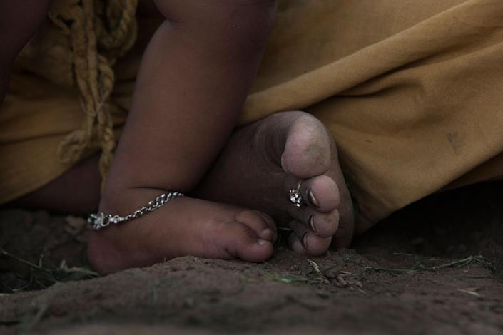 <p>Arti Khatik's foot and her child's. She is wearing a wedding ring around her toe. She is 16 and started living with her husband two years ago. She has a good relationship with her mother-in-law, but she can't stand her husband who drinks and doesn't treat her well. They sit on a field in Changedi, Udaipur, Rajasthan, India in July 2016. (Photo: Rafael Fabrés) </p>