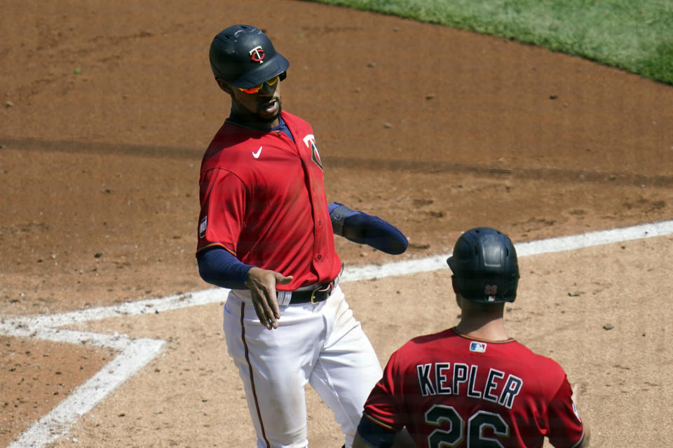 Minnesota Twins' Byron Buxton, left, scores on a two-run single by Minnesota Twins' Willians Astudillo in the third inning of a baseball game, Thursday, May 6, 2021, in Minneapolis. At right is Twins' Max Kepler. (AP Photo/Jim Mone)