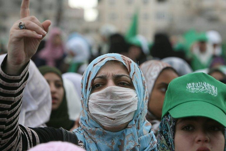 A Hamas supporter wearing a protective mask against swine flu at a rally in Gaza City on December 14, 2009