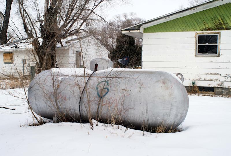 In this Thursday, Feb. 6, 2014 photo is a propane tank outside a home on the Standing Rock Reservation in Fort Yates, N.D. The reservation is on the wind-swept Northern Plains where there is little to block the icy gales that whip in from the northwest and create wind chills as low as 50 below. Many residents live in homes, some with ill-fitting doors, others with boards tacked up where the windows should be, or deteriorating roofs that leak much-needed warmth. (AP Photo/Kevin Cederstrom)