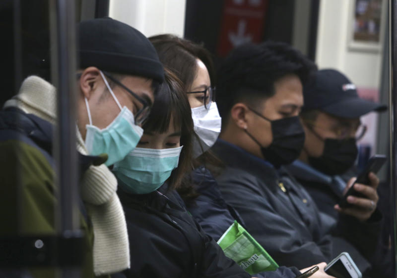 People in Taiwan wear protective face masks at a metro station in Taipei, Taiwan, Sunday, Feb. 9, 2020. China's virus death toll rose by 89 on Sunday to 811, passing the number of fatalities in the 2002-2003 SARS epidemic, but fewer new cases were reported in a possible sign its spread may be slowing as other nations stepped up efforts to block the disease. (AP Photo/Chiang Ying-ying)