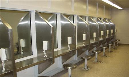 A bank of telephones and reinforced glass windows to separate convicts from their visitors are seen at a visitation center of the Mississippi State Penitentiary in an undated photo provided by the Mississippi Department of Corrections in Parchman, Mississippi. REUTERS/Mississippi Department of Corrections/Handout via Reuters