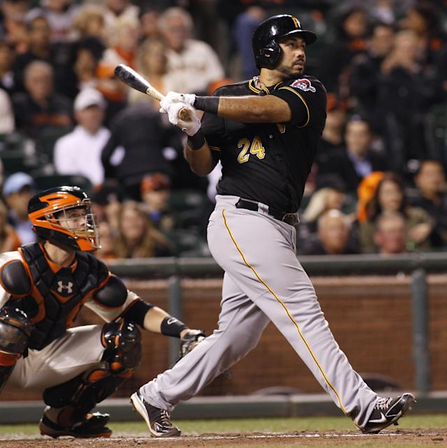 Pittsburgh Pirates' Pedro Alvarez hits a two RBI double against the San Francisco Giants during the fifth inning of an MLB National League baseball game in San Francisco, Thursday, Aug. 22, 2013. At left is Giants' Buster Posey(AP Photo/George Nikitin)